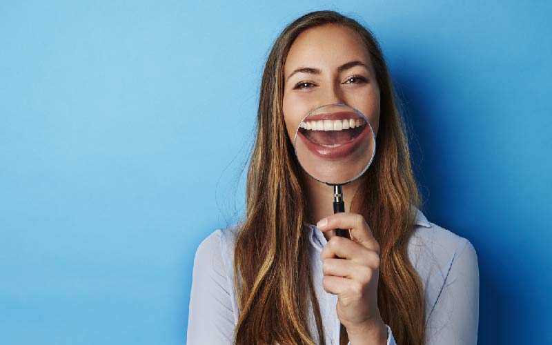 woman smiling holding up magnifying glass
