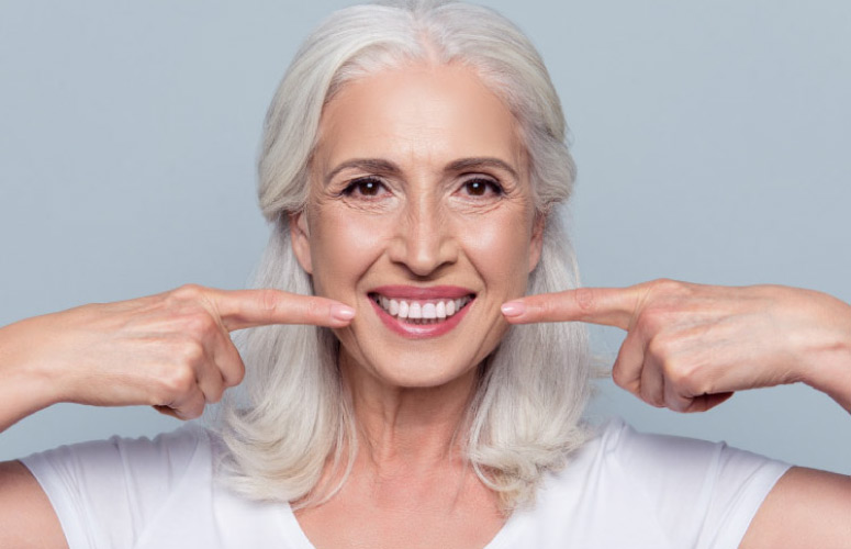 white haired woman points to her white teeth with both index fingers