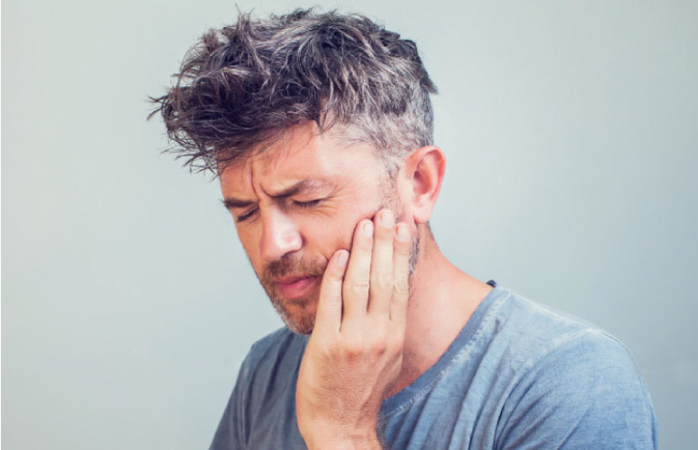 man holding his jaw with intense tooth pain