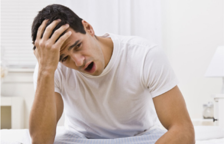 man wakes up sleepy after suffering from sleep apnea