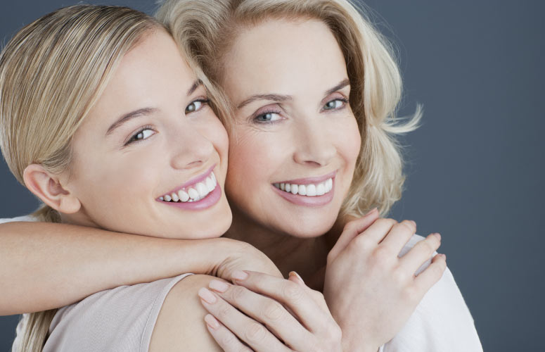 two blond women hug and smile while showng off their white teeth