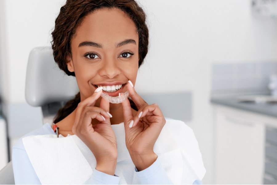 young woman inserts a clear aligner to straighten her teeth