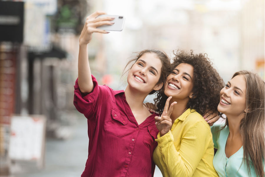 three young women take a selfie to show off their smiles
