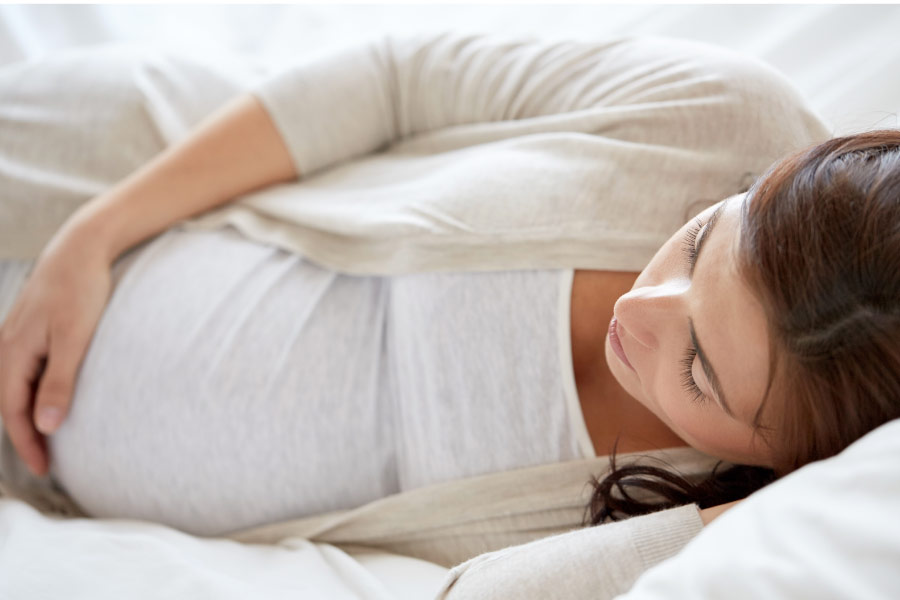 pregnant woman laying on her side holding her belly